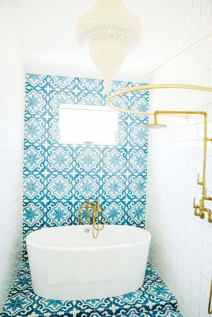This small, vibrant bathroom shows off a colorful, patterned accent wall and tile flooring along with a Moroccan pendant light fixture.