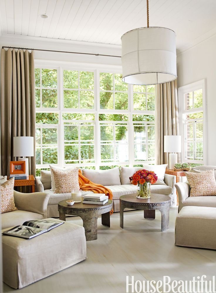 """""""I think there's peace in balance,"""" says designer Kay Douglass, who furnished the family room of an Atlanta house with two Charlotte chairs and ottomans, two vintage iron coffee tables found at a fair in France, two table lamps, and two vintage side tables that belonged to the owners — lacquered in Orange Spice to give them new life. Thibaut sofa, Iron and Linen Frame light fixture, and orange picture frame from South of Market. Belgian linen curtains from Lewis & Sheron Textiles…"""