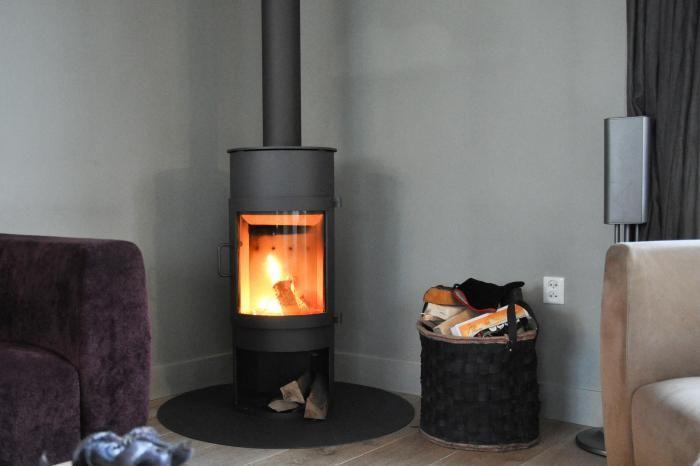 Moderne ronde vrijstaande kachel op hout, in de hoek geplaatst op een vloerplaat   Profires partner Jos Harm · inspiratie voor sfeerverwarming