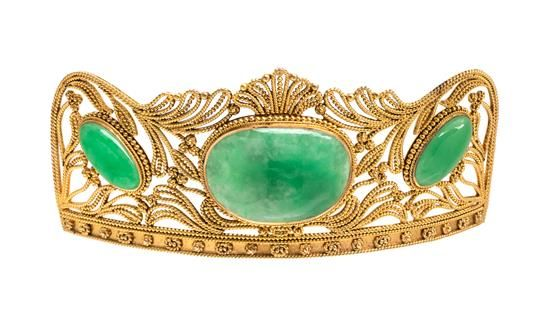 A Yellow Gold and Jadeite Hair Ornament, Late Qing Dynasty, containing an oval cabochon saddle cut mottled green jade measuring approximately 31.50 x 23.00 x 4.80 mm and two oval cabochon cut green jade measuring approximately 19.00 x 10.50 x 4.40 mm within an open wirework rope texture foliate motif surround. Stamp: 14K (maker's mark).