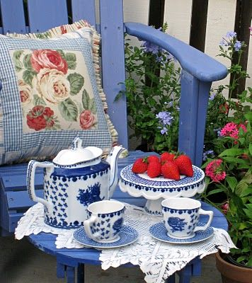 cute tea set in a garden setting, pretty blue with a dash of red, love!