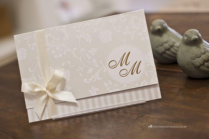 Convite com arabescos florais e monograma em hot stamp dourado.