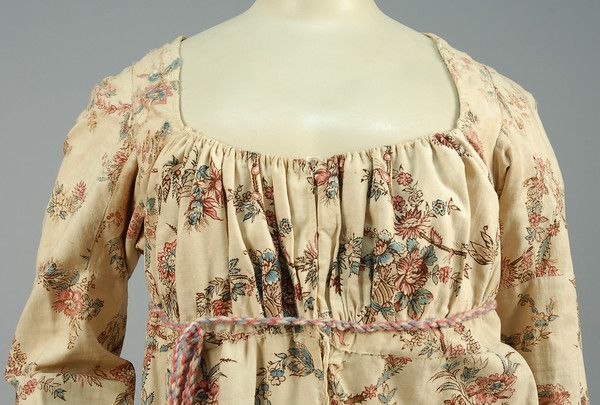 Printed Cotton Gown, Bodice Detail, 1800-05.   Empire line, scooped neckline, gathered bodice, long straight sleeves.  Cream with scrolling polychrome floral, high waist with belt loops, flared skirt pieced side gores, muslin bodice lining with front closure.