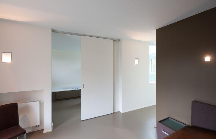 Witte plafondhoge schuifdeur met aluminium rail en volkern paneelafwerking