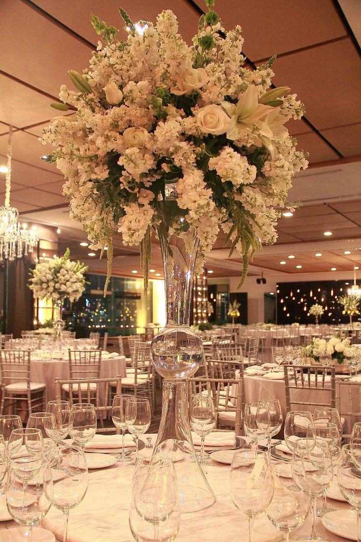Elegante centro de mesa alto en combinación de flores blancas.