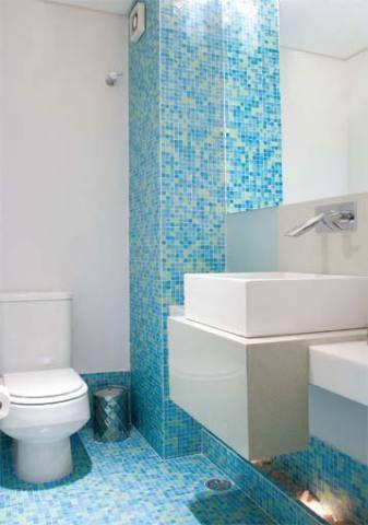 Pastilhas de vidro azuis e verdes cobrem o piso, o rodapé e uma coluna no canto do lavabo. Projeto de Vera Dantas.  http://casa.abril.com.br/materia/lavabos-coloridos#10