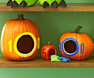 Pumpkin Toss Game - Hollow out three pumpkins: small, medium and large -- then cut large holes into the front of the pumpkins and paint a ring around the border of the hole. Paint point values onto the face of each pumpkin. Place them at different distances and use a beanbag to play!