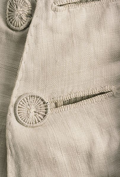 "Detail buttons, waistcoat, probably England, Plain weave bleached white linen, quilted to shape with intricately corded designs, ""French closure"" with wire and thread-work buttons, linen lining."