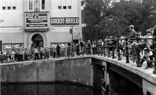 Nova Bioscoop in Amsterdam op de hoek van de Prinsengracht en de Leliegracht. Een lange rij kinderen staat te wachten op de brug voor het bioscoopgebouw waar op de tekst 'Groot-Beeld' staat. Amsterdam, [circa 1957].