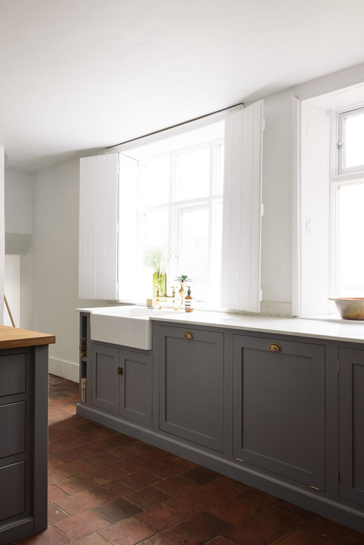 Simple grey shaker cupboards, white walls, terracotta tiles and brass hardware in this lovely deVOL Kitchen
