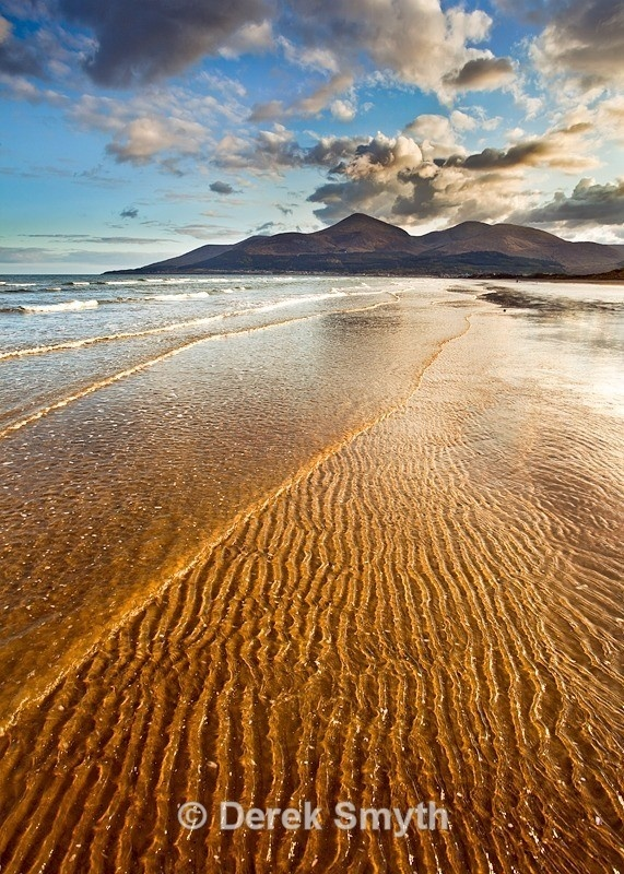 The strong setting sun creates a nice golden cast to the gentle ripples lapping up Murlough Beach on Dundrum Bay in County Down Northern Ireland.