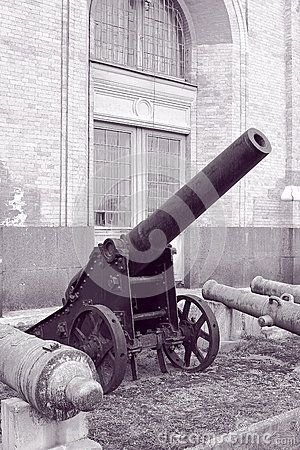 The fortress cannon of the 19th century on a gun carriage and the barrels of the old bronze cannons, stacked near the wall of the Museum building. The territory of the Military-historical Museum of Artillery, engineer and signal corps. St. Petersburg, Russia
