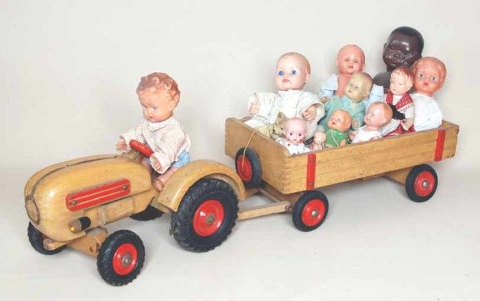 A tractor pulling a wagon full of old dolls.