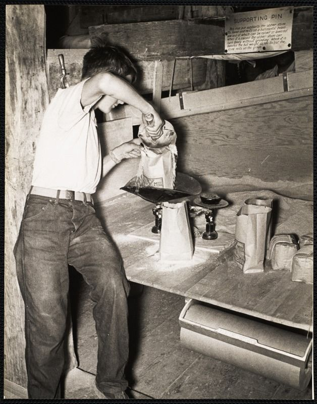The Old Mill, Nantucket - packaging the newly ground cornmeal, c. 1930s.  https://www.digitalcommonwealth.org/search/commonwealth:cc08hq404 #windmill