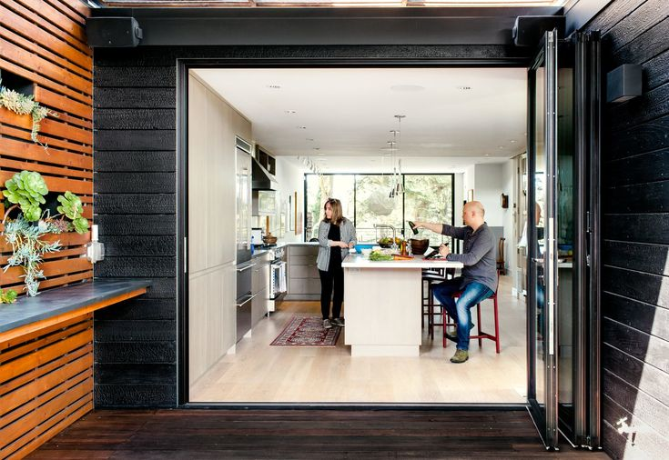 Scott and Regina's toolkit of electronics extends outdoors. A Sonos sound system is installed on the patio and a retractable sunshade from DeFauw Design protects the kitchen cabinets' gray Tabu veneer from fading.