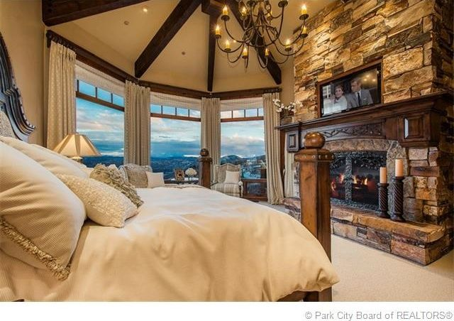 Rustic Master Bedroom With Carpet Stone Fireplace Chandelier High Ceiling Rustic Fireplaces