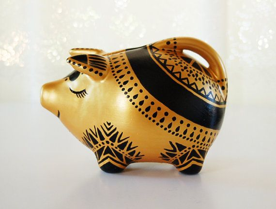 Bring home a one of a kind piece of decorative and functional art with this hand-painted piggy bank. Intricately painted bold black details create a striking appearance against the gold base. Fantastic addition to any collection or as a gift for an animal-lover. Materials: Ceramic piggy bank. Hand-painted gold and black artist grade acrylic paint. Finished with a non-toxic clear glaze. Size: 4.25 high, 6.25 long, 4 wide Care: For indoor use only. Dust with a soft non-abrasive cloth. If ...