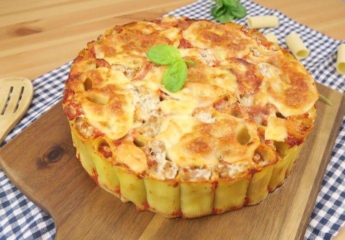 La torta di rigatoni è un modo davvero unico e originale per servire la pasta al forno. Si presenta benissimo ed è la ricetta perfetta per fare colpo sui vostri ospiti!  GLI INGREDIENTI  500g di rigatoni 500g di salsa 500g di ricotta 500g di carne macinata sale pepe 1 mozzarella (250g) parmigiano basilico  LA PREPARAZIONE  Cuocete i rigatoni molto al dente (circa6/7 minuti), scolateli e amalgamateli con due cucchiai di parmigiano. Disponeteli in modo verticale nella tortiera poi farciteli…