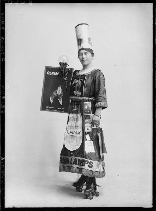 "Ref: 1/2-049688-G  Woman, on roller skates, advertising Osram light bulbs. Shows her wearing a hat decorated with pictures of street lamps and holding a poster that reads: ""Osram. Last longest - beat gas"". Other posters are attached to her dress. Photograph taken circa 1915-1922, by Steffano Webb of Christchurch."
