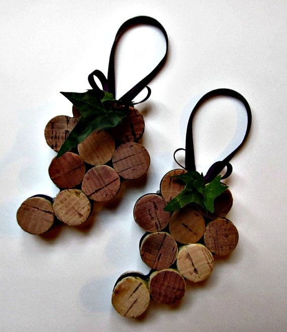Upcycled wine corks have been cut in half, glued together and adorned with purple ribbon and green leaves to create great little grape bunches!