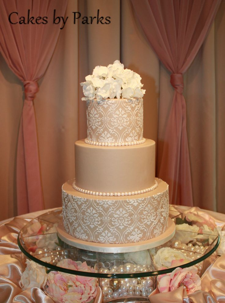 i like how the cake is raised up with flowers and pearls underneath it