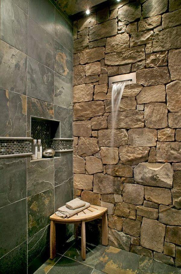 Piedra natural en las paredes de la ducha, un estilo moderno, pero rústico muy adecuado al ambiente.