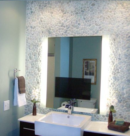 Celebrity designer and contractor Matt Muenster transformed a small, plain bathroom into a luxurious spa-like getaway. Pale blue-green walls and a pebble rock wall above the vanity set the stage for serenity. With a TV mirror, there's no reason to leave this oasis.