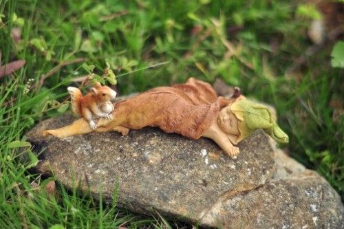 A fairy baby sleeps nestled in a fallen leaf watched over by a woodland squirrel.
