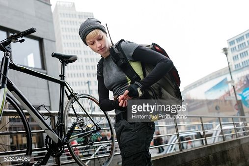 Female bike messenger locking her bicycle on a fence