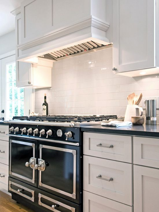 Gorgeous Kitchen With La Cornue Cornufe Range In Gloss Black And White Wood Paneled Hood