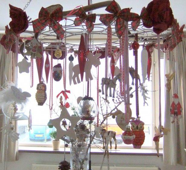Deze simpele creatie is gemaakt aan de hand van een ijzeren krans waaraan verschillende kerstvoorwerpen aanhangen. Met verschillende linten zijn deze in hoogtes opgehangen.