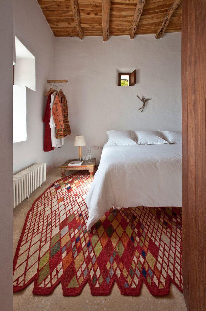 В спальне простые оштукатуренные и побеленные стены, бетонные полы и тщательно подобранный ковер. .