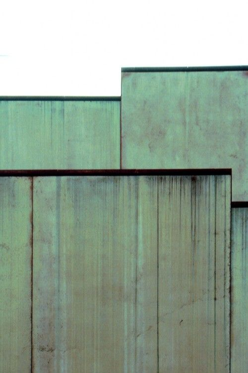 """The walls are clad with large pre-fabricated slabs of concrete. Mixed with pulverized limestone and copper, the principal materials used to build the villa, the concrete cladding will turn green.  Water enriched with copper ions running down the façade will accelerate the change. Through this compressed process of patinization, the new building will make a journey in time to the meet the genius loci.""  Gigon Guyer, Oskar Reinhart Collection Am Römerholz, Winterthur, Switgzerland, 1998.."