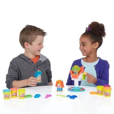 Knabe und Mädchen spielen mit PlayDoh Knete Frisierspass