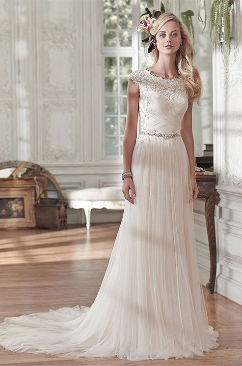 Comprised of barely-there tulle, this stunning sheath wedding gown sparkles with a delicate Swarovski crystal belt at the waist. Maggie Sottero, Spring 2016