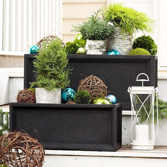 You can make greenery baskets by grouping together a few seasonal items including bits of greenery, twig balls, wood pieces, and some leftover ornaments. Put one basket on each of your entryway steps or leave one by the front door.