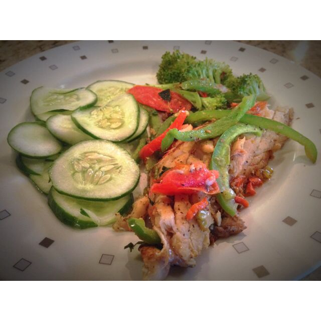 Salmon mixed sweet peppers and tomatoes with cucumbers and broccoli at the side