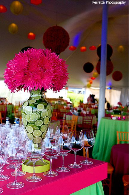 Limes in vase with hot pink flowers. Striking centerpiece.