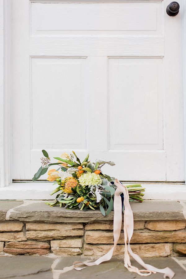 Flowers on Broad Street arranged an earthy yet bright bouquet for the occasion. It included pincushion proteas, hydrangeas, parrot tulips, golden berries, dusty miller, and seeded eucalyptus tied with raw silk ribbons. | Photo by Radian Photography