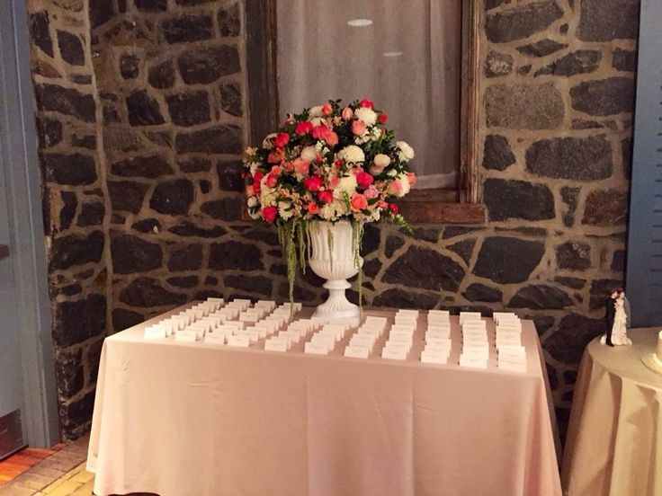 Attractive coral and cream flowers create an impressive accent on Amanda and Anthony card table at Rockwood Carriage House. Greenery Caterers. Dazzle Photography.