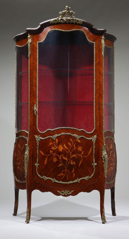 A Louis XV style gilt-metal-mounted kingwood and floral-marquetry vitrine cabinet, the arched crest centered by a pierced rocaille clasp over a bombe case with central arched door with curved Plexiglas panel over a floral spray, enclosing a shelf, with curved Plexiglas panels and similar decoration to sides, on foliate-headed cabriole legs ending in similarly cast sabots.
