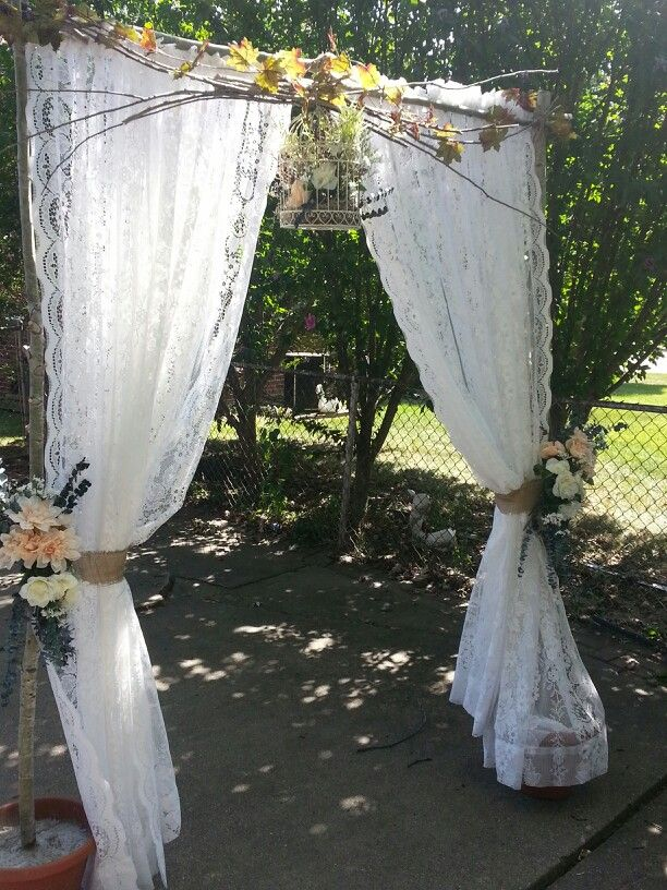 Wedding arch I made for daughters wedding. Repurposed curtains,downed tree limbs, dollar tree flowers#wedding arch
