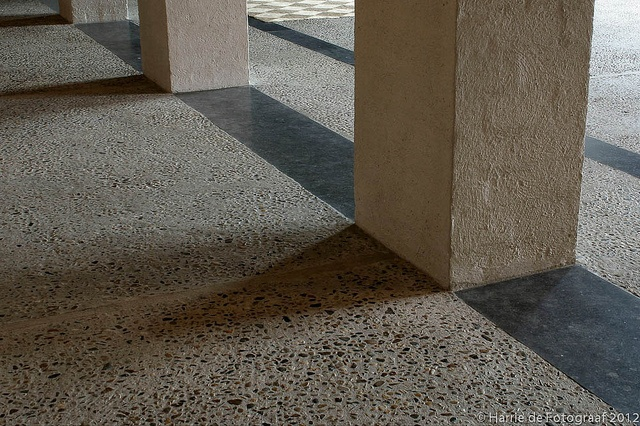 View of the washed concrete floor and cemented brick column inside the house of the Dutch architect Jan de Jong in Schaijk. Nice to see how the architect choose his material palette in such a way to bring out the play of light. Photo by Harrie de Fotograaf.