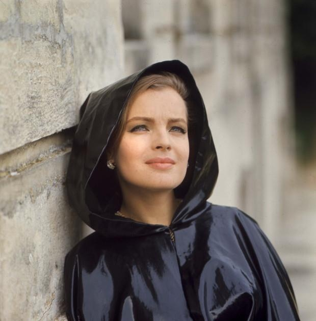 Romy Schneider in black shiny hooded cape. Matte smokey nude makeup with slightly winged eyeliner of the 60s.