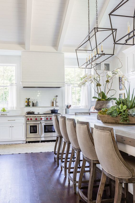 Kitchen Island Lighting. itchen features a pair of Darlana Linear Pendants illuminating a white center island with turned legs topped with butcher block lined with gray linen counter stools, Restoration Hardware 19th C. French Empire Stools. A kitchen sin