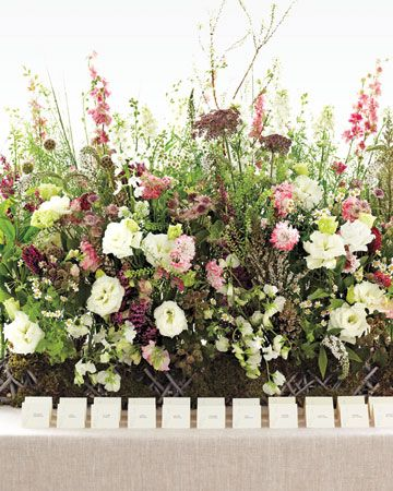 A gorgeous hedgerow of flowers used to dress a table of escort cards.