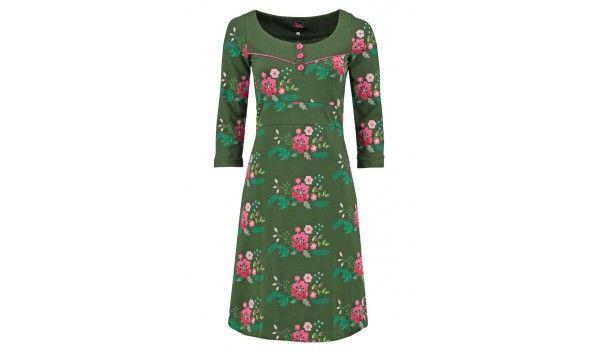 Groene jurk van Tante Betsy met allover bloemenprintje in het roze. De hals en de driekwart mouwen zijn uni groen en er loopt een roze biesje over de borst, met roze knoopjes. Vanuit de taille loopt de rok uit in een A-lijn en het model valt tot net op of boven de knie.
