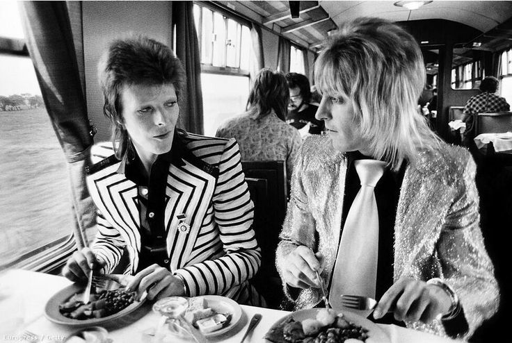 David Bowie and Mick Ronson enjoy lunch on the train in 1973.