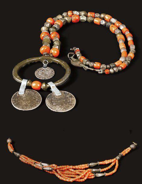 Deux colliers, le premier à plusieurs rangs de corail intercalés de perles oblongues en argent, et le second à rang simple agrémenté, en guise de pendentif, d'une boucle d'oreille ancienne ornée de pièces… - Pierre Bergé & associés - 28/05/2008