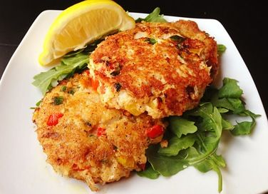Crab cakes served over baby arugula and drizzled with a lemon vinaigrette